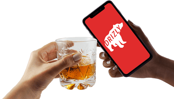 Hand holding a whiskey glass, bumping it up against a hand holding a phone showing the Drizly logo.