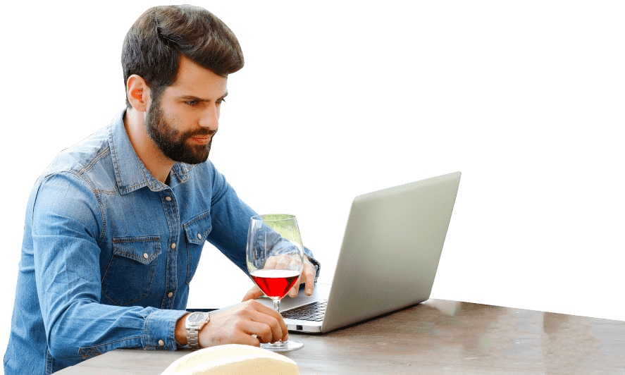 Guy drinking wine looking at a laptop