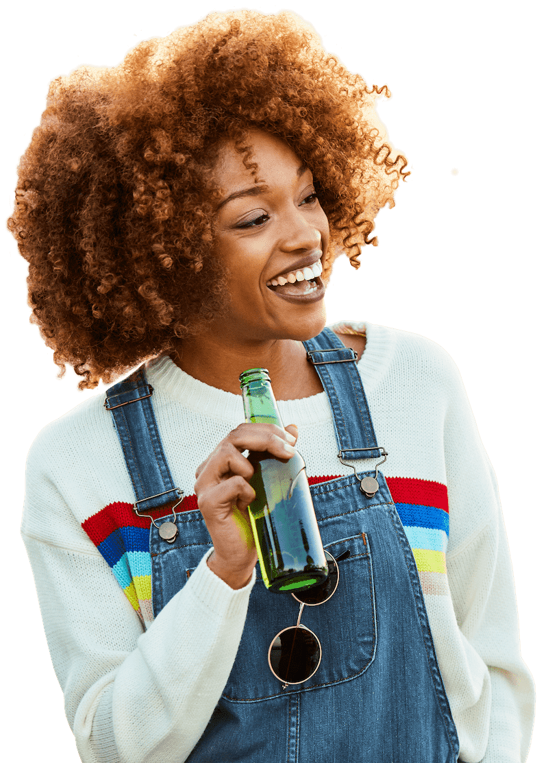 girl wearing overalls and smiling while holding a beer